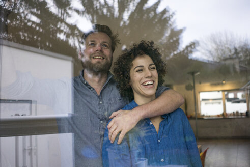 Happy couple behind window at home looking out - JOSF02734
