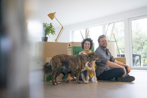Happy couple sitting in living room with dog and cardboard boxes - JOSF02737
