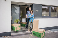 Couple standing at house entrance with cardboard boxes - JOSF02743