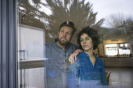Serious couple behind window at home looking out - JOSF02746