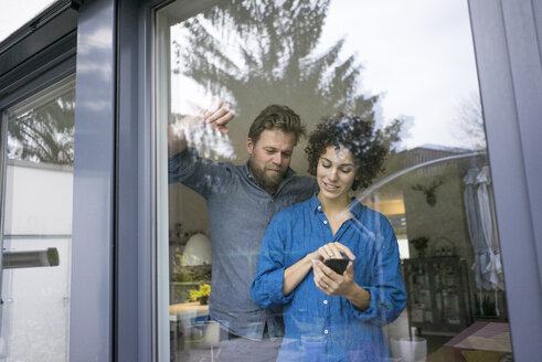 Couple behind window at home using cell phone - JOSF02749
