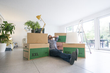 Man sitting on the floor in living room surrounded by cardboard boxes - JOSF02758