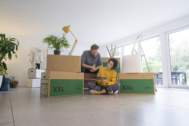 Couple sitting in living room with cardboard boxes using tablet - JOSF02761