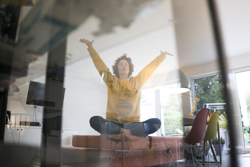 Woman sitting on couch at home in yoga pose - JOSF02767