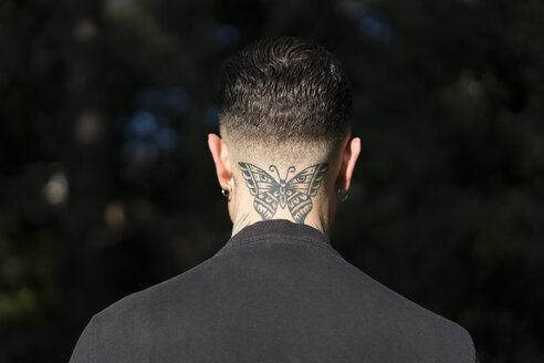 Back view of man with tattooed butterfly on his neck - XCF00182