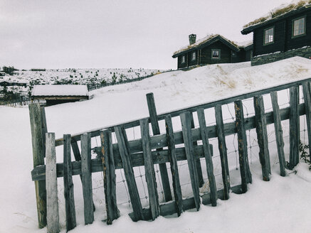 Norway, Rondane, Traditional Cabins in Norwegian Mountain Resort on Overcast Winter Day - JUBF00292