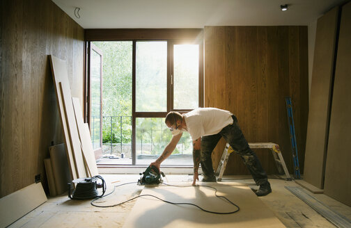 Construction worker using electric saw to cut wood in house - HOXF04236