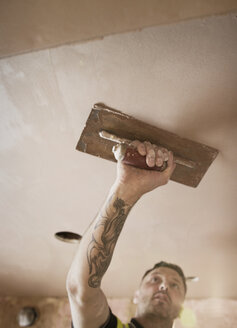 Construction worker with tattoo plastering ceiling - HOXF04257
