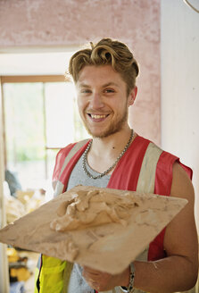 Portrait smiling, confident young construction worker plastering - HOXF04266