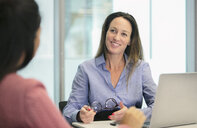 Smiling, confident businesswoman listening in conference room meeting - HOXF04287
