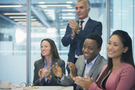 Business people smiling and clapping in conference room meeting - HOXF04308
