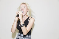 Young woman singing into microphone - CAIF22402