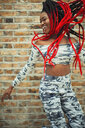 Carefree young woman in camouflage clothing dancing against brick wall - CAIF22414