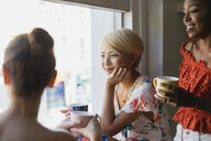 Young women friends drinking coffee at apartment window - CAIF22465