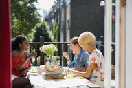 Young women friends eating brunch on sunny apartment balcony - CAIF22480