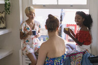 Young women friends drinking coffee and talking in apartment window - CAIF22486