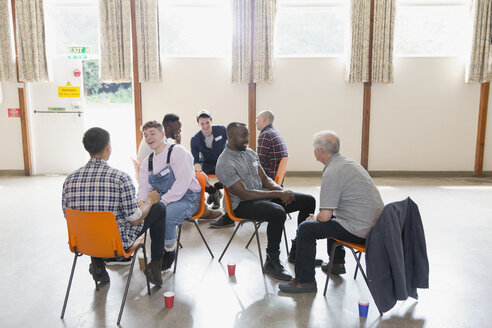 Men talking in group therapy in community center - CAIF22526