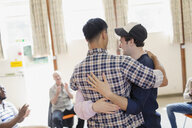 Men hugging in group therapy - CAIF22544