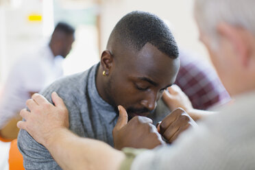 Man comforting young man in group therapy - CAIF22547
