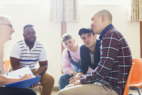 Attentive men talking and listening in group therapy - CAIF22550