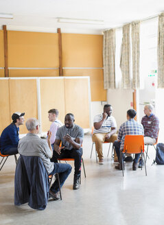 Men talking in group therapy in community center - CAIF22553