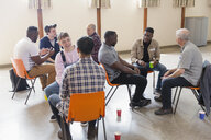 Men talking in group therapy in community center - CAIF22556