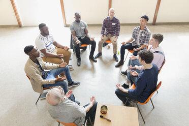 Men praying in circle in prayer group - CAIF22562