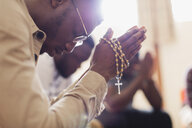 Man praying with rosary in prayer group - CAIF22565