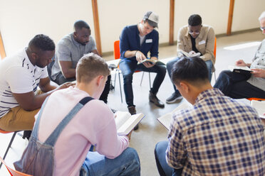 Men reading and discussing bible in prayer group - CAIF22586