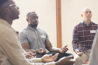 Men praying with eyes closed in prayer group - CAIF22592