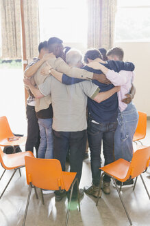 Men hugging in huddle in group therapy - CAIF22598