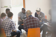 Men reading and discussing bible in circle in prayer group - CAIF22601