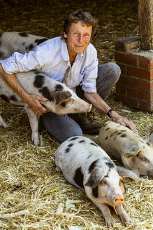 Smiling senior woman kneeling in barn with Gloucester Old Spot pigs. - MINF09838