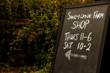 Close up of Sandy Lane farm shop blackboard with opening times. - MINF09871