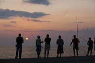 Fishermen trying their luck, standing on the railing of the Malecon harbour wall in Havana, Cuba - MINF09898