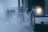 Partial view of large commercial truck driving in hazardous conditions of snow and rain on a freeway. - MINF09943