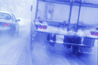 Partial view of large commercial truck driving in hazardous conditions of snow and rain on a freeway. - MINF09946