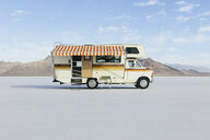 Vintage Dodge Sportsman RV with striped canopy parked on Salt Flats - MINF09994