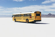 Yellow school bus driving on Salt Flats - MINF10015