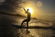 Indonesia, Bali, Canggu, silhouette of surfer at sunset - KNTF02592