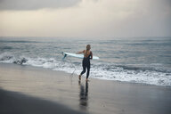 Indonesia, Bali, Canggu beach, surfer with surfboard at the beach - KNTF02598