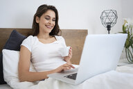 Woman having coffee in bed using laptop, laughing - BSZF00820