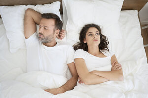 Frustrated couple lying in bed - BSZF00835