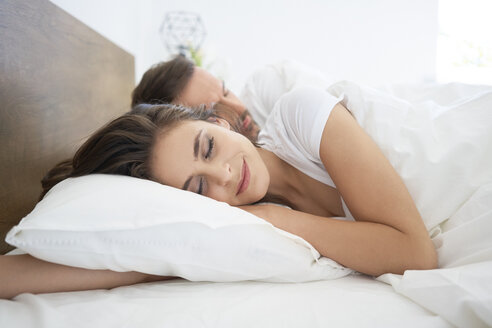Sleeping couple in bed, woman smiling - BSZF00838
