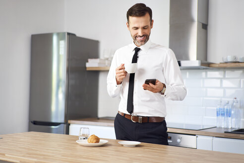 Man standing int he kitchen  in the having coffee and looking at his phone before work - BSZF00841