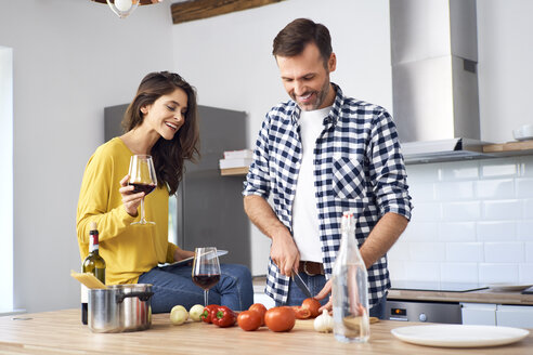 Affectionate couple in kitchen, preparing spaghetti toghether, drinking red wein - BSZF00844
