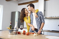 Affectionate couple in kitchen, preparing spaghetti toghether - BSZF00847