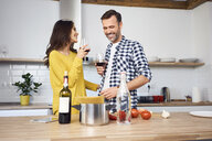 Affectionate couple in kitchen, preparing spaghetti toghether, drinking red wein - BSZF00850