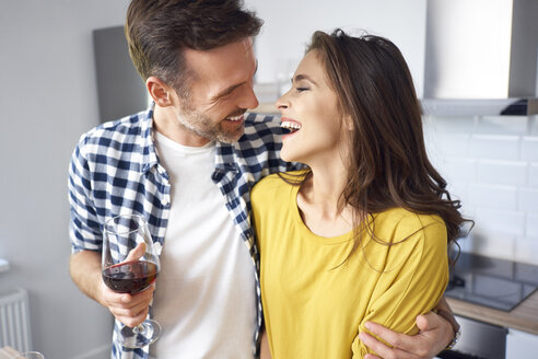 Happy couple standing in kitchen, with arms around, drinking red wine - BSZF00862