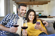 Couple sitting in living room, drinking red wine, using smartphone - BSZF00865